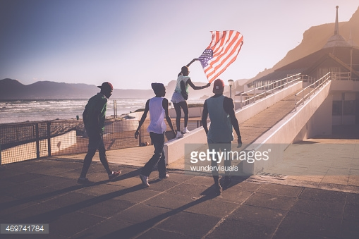 Teenage African American teenager flying an American flag at beach